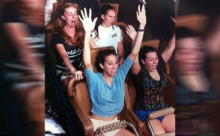 A girl looking very scared with three other girls on a roller coaster