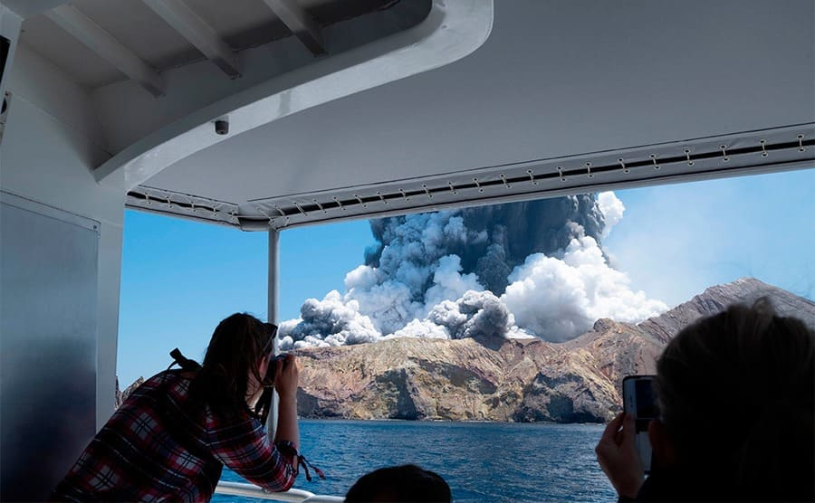People in the boat photographing the eruption with a large cloud of smoke coming out of the mountain