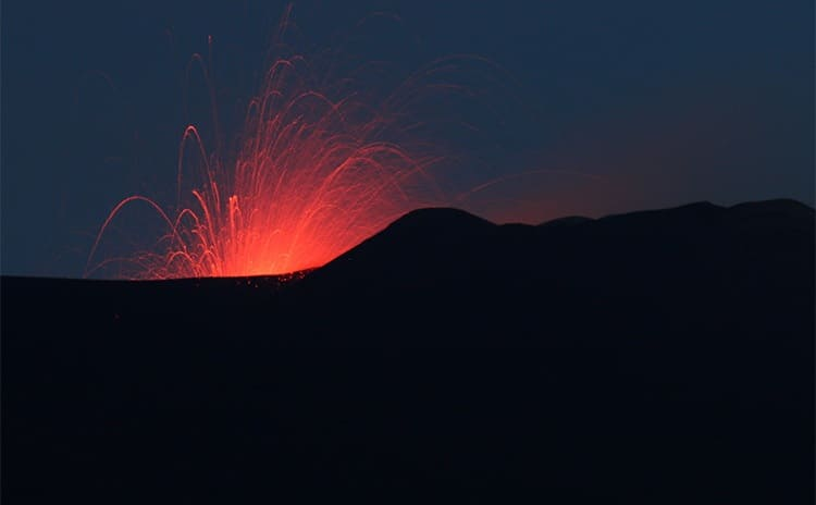 Some lava spewing out of a volcano at night