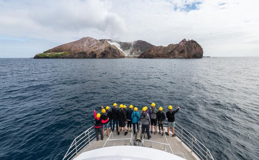 Tourists on a boat wearing hard hats on the way to White Island