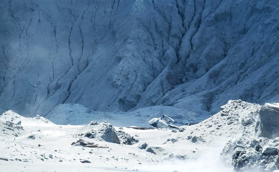 A helicopter sitting on the shore on the white ash-covered mountain