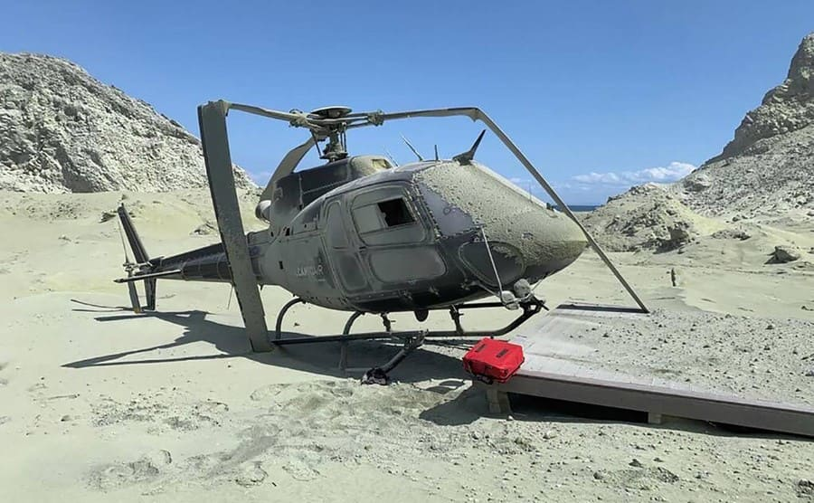 A helicopter sitting on ash-covered in ash on White Island
