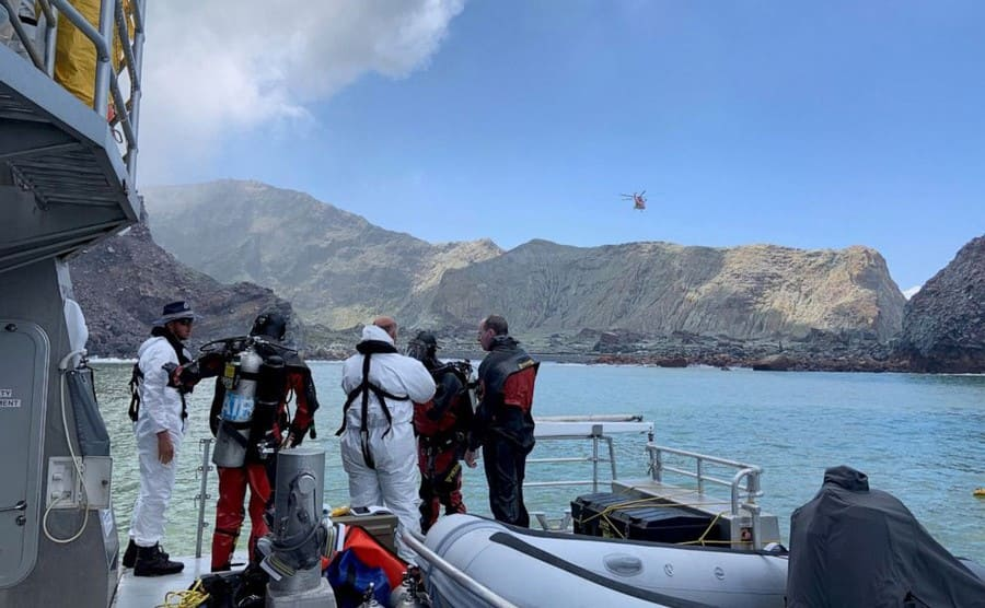 Divers on a boat near White Island with a helicopter flying above