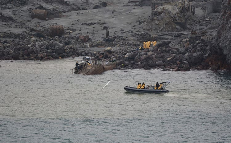 Rescue workers in yellow suits and gas masks on the shore of White Island