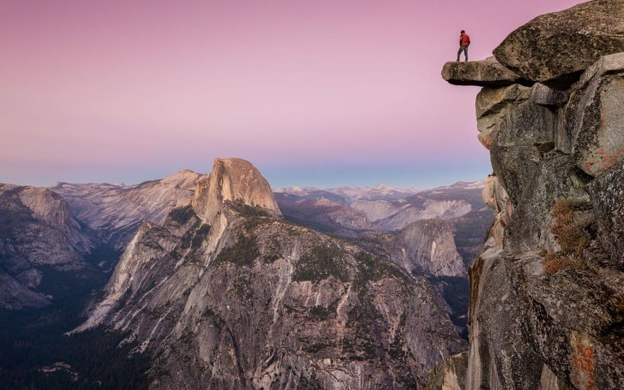 A male hiker is standing on an overhanging rock at Glacier Point, Yosemite National Park, California
