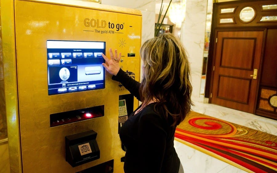 A woman uses the 'Gold To Go' vending machine