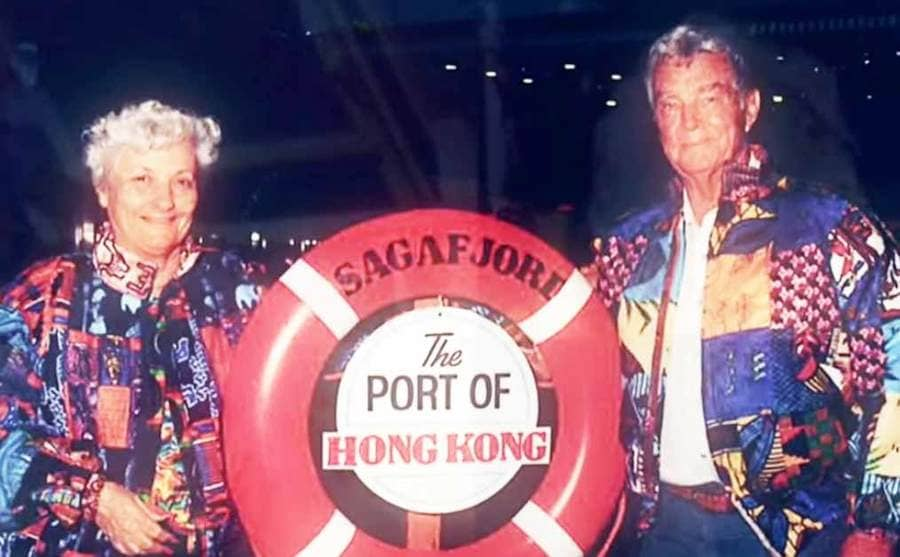 Lee Wachtstetter and another man holding a buoy that says The Port of Hong Kong