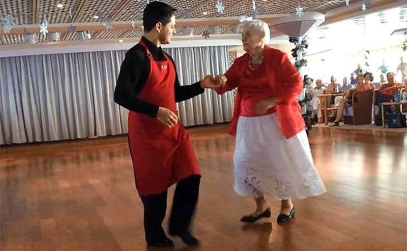 Lee Wachtstetter and a waiter dancing on an open dance floor during a cruise