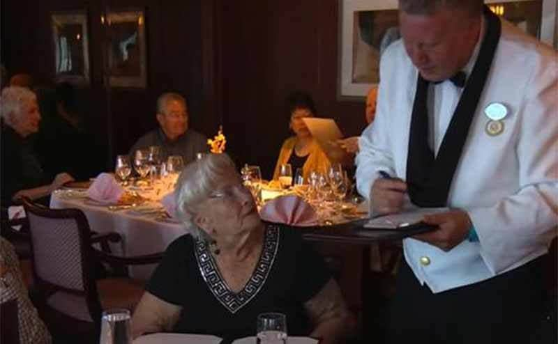 Lee Wachtstetter having her order taken in a cruise ship dining room