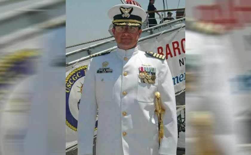 A navy captain standing in his service dress blue uniform
