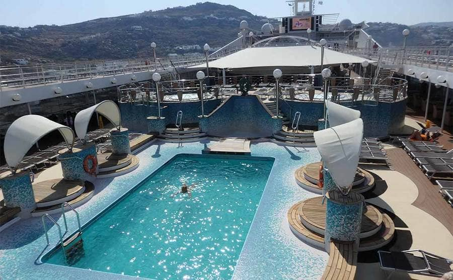 A photograph of the deck with a swimming pool and an area to lounge on a cruise ship