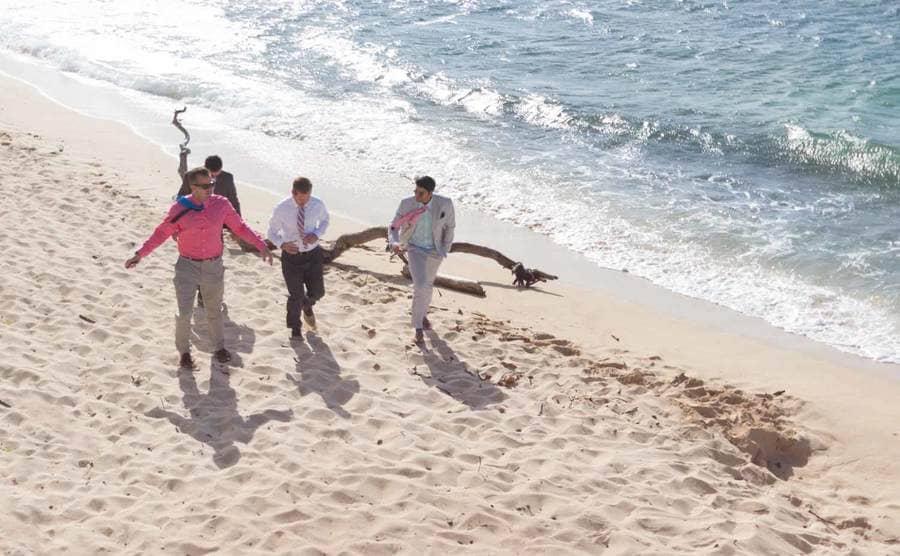 Men in suits walking along the shoreline in Hawaii