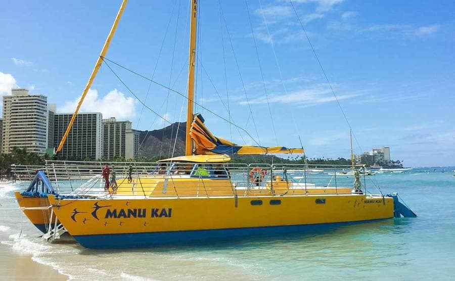 A photograph of a boat sitting on the shoreline in Hawaii
