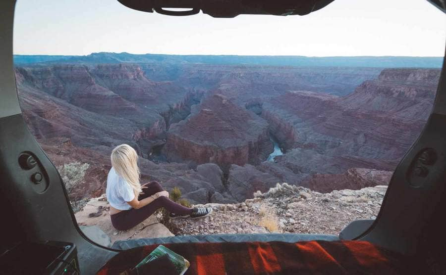 Christian sitting outside of her SUV with a view of the open mountains behind her