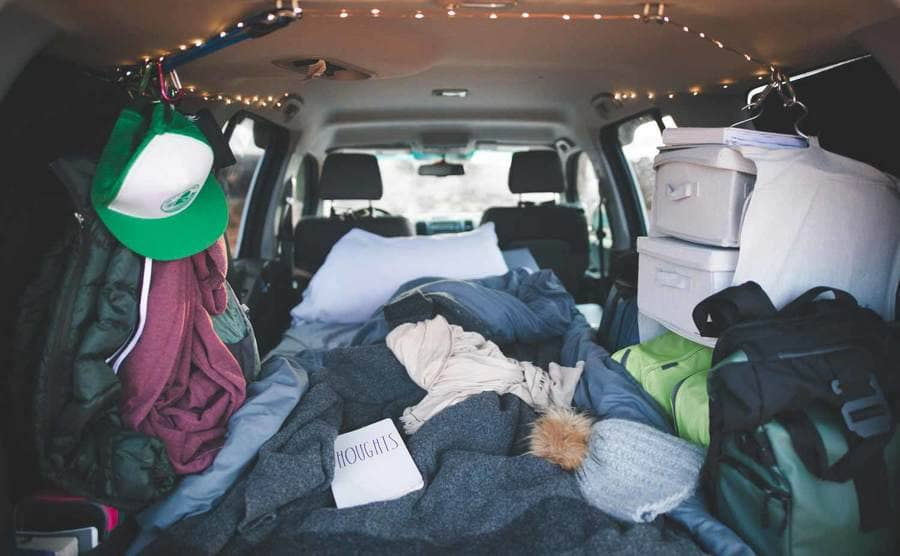 A view of the inside of Christian's SUV with her belongings hung on the sides and a small bed in the middle