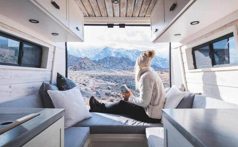 Christian sitting in the window seat in the back of her van reading a book with a mountain view behind her