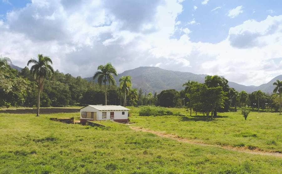 A photograph of a large open field with a small house leading up to green forest and mountains behind it in the Dominican Republic