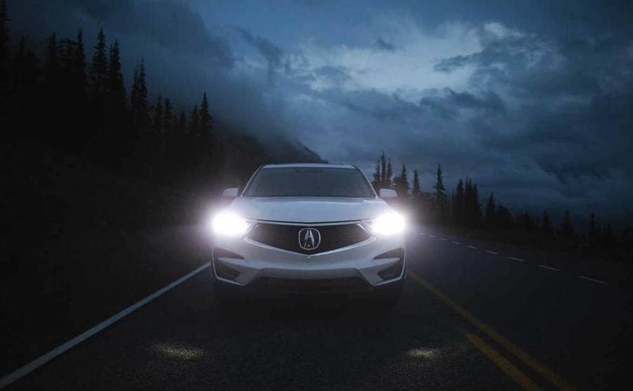 A photograph of an Acura car on a dark road at night with the headlights on