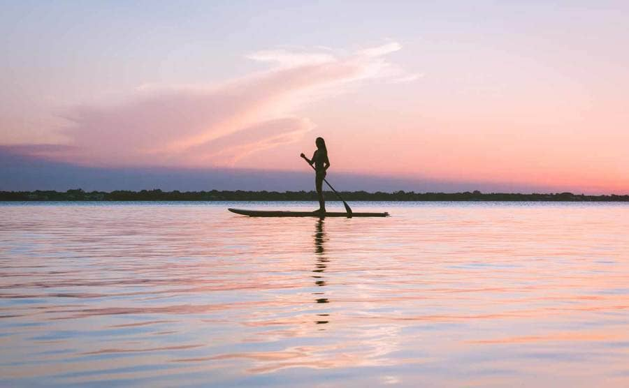 A photograph of a model on a paddleboard in the water with pink, orange, and purple lighting from the sunset