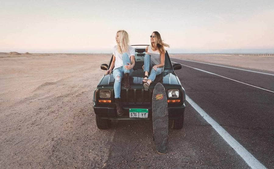 Two blonde women sitting on the hood of a Jeep with an Egyptian license plate on the side of an open road