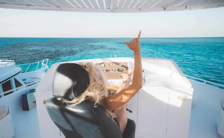 Christian sitting behind the wheel of a yacht with her feet up