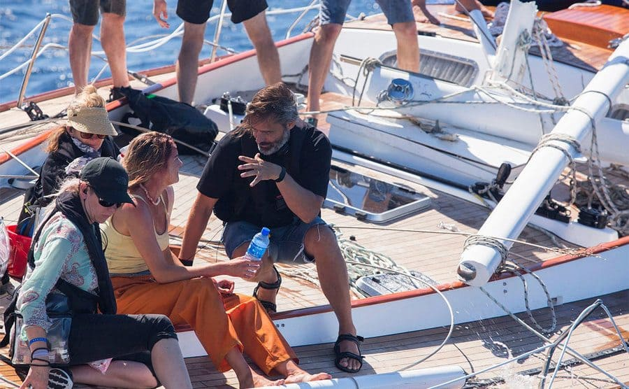 Shailene Woodley and Baltasar Kormakur sitting together on a boat, and the film crew is around them