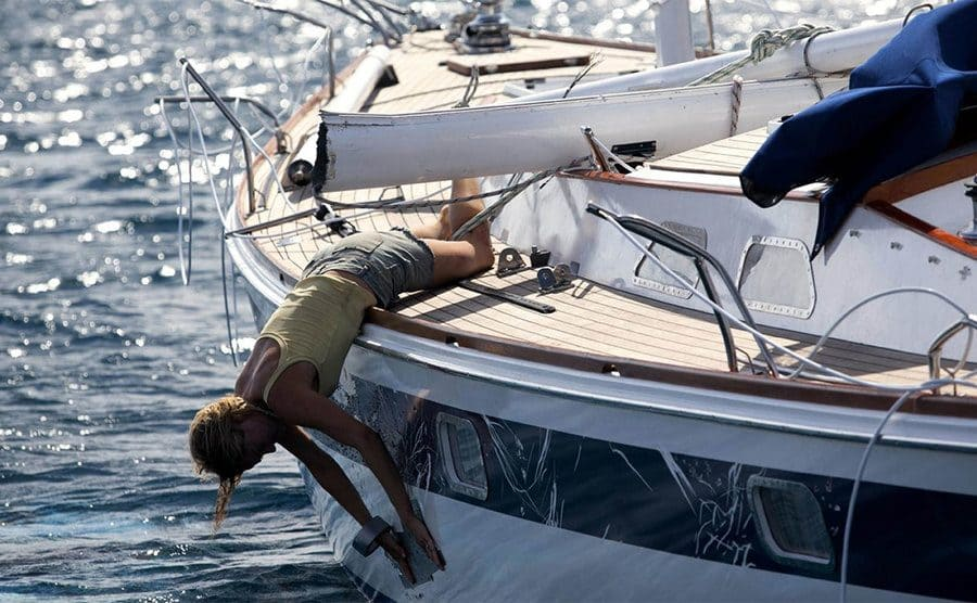 Shailene Woodley hanging upside down from the boat fixing it