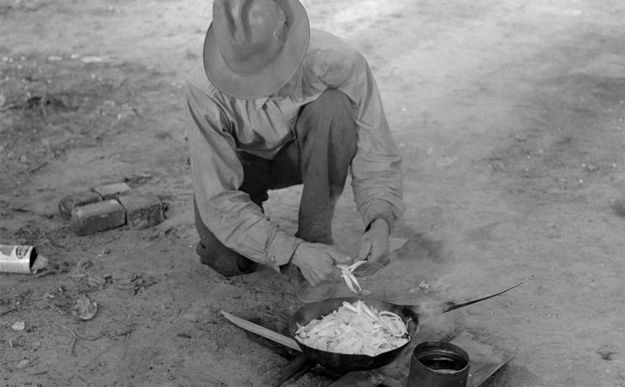 A man cooking food over a fire in the wilderness