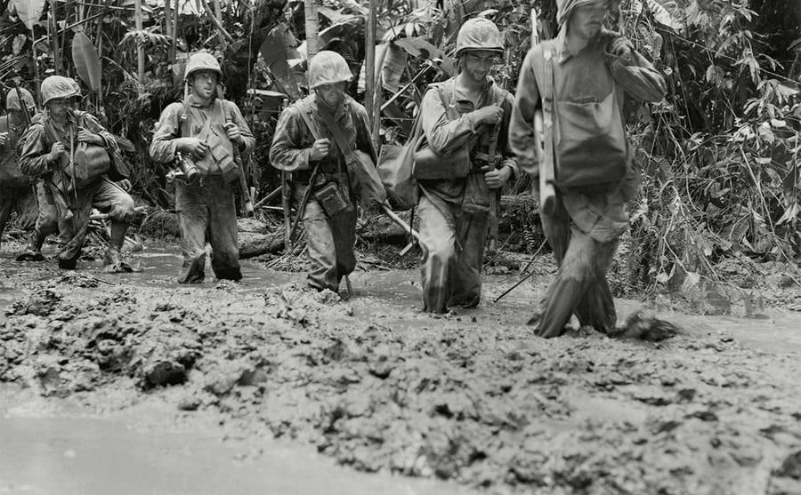 US Marines walking through thick mud
