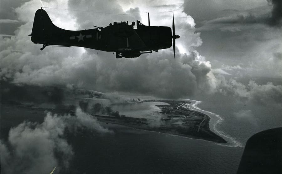 A military aircraft flying over an island