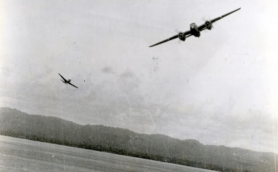 Fighter planes flying above a field with a forest in the background