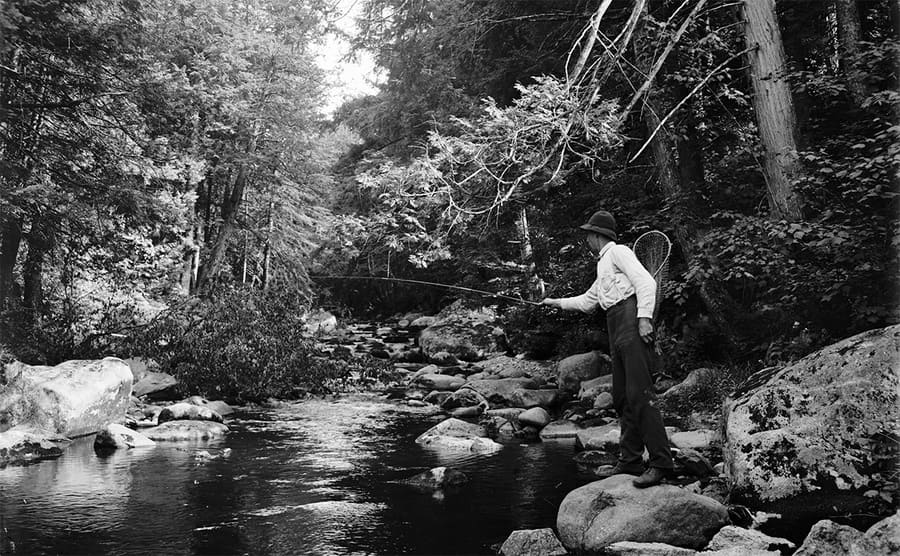 A fisherman by a stream