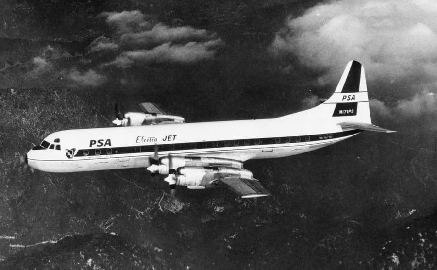An Electra jet photographed flying over mountains in the '60s