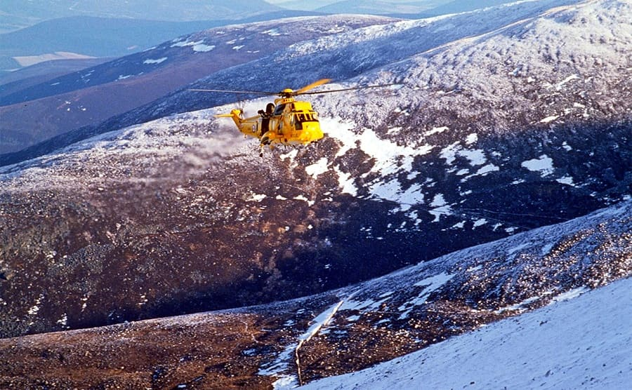 A rescue helicopter flying above a mountainous landscape