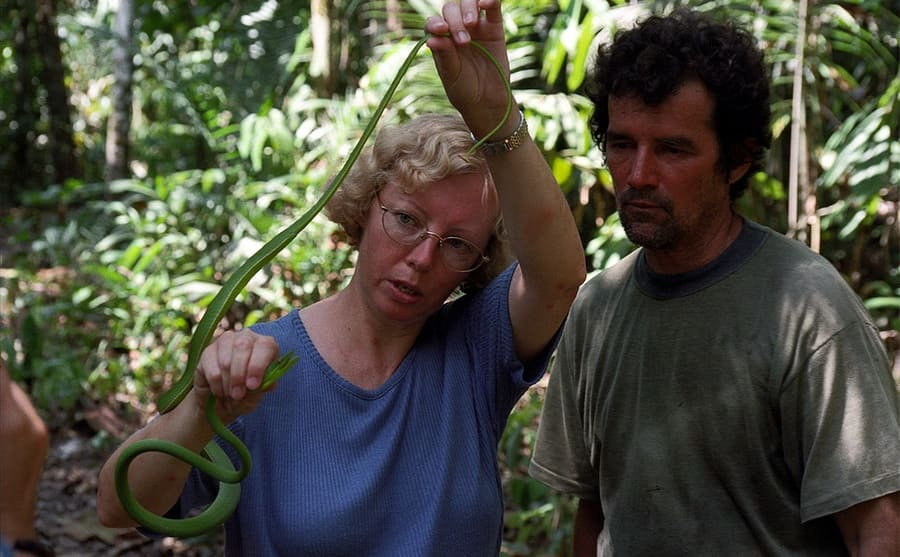 Juliane visiting the site of the crash showing someone a snake in the rainforest