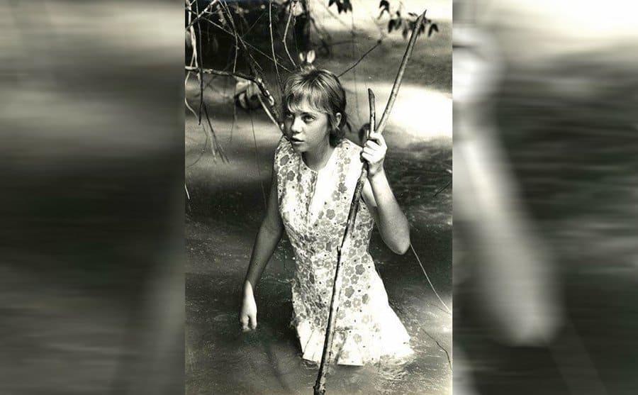Juliane walking through shallow water using a stick to help walk