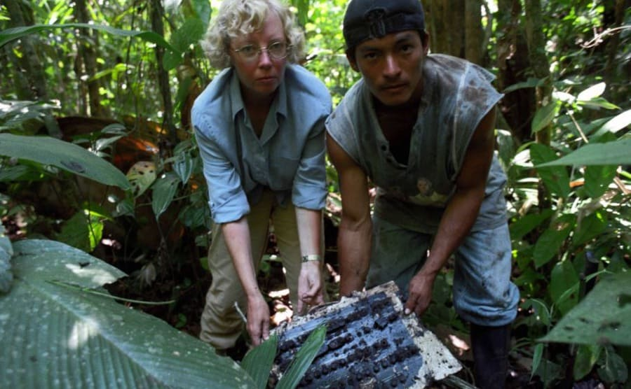 Juliane and a man holding up a piece of the plane that they found in the Amazon