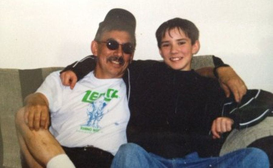 Caleb and his father posing on the couch together when he was a young boy