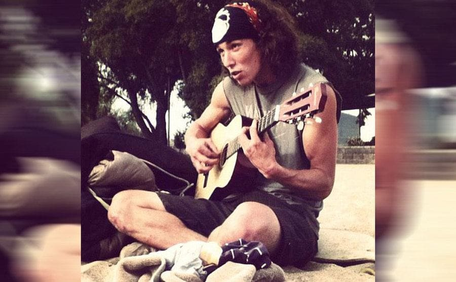 Kai playing the guitar outdoors