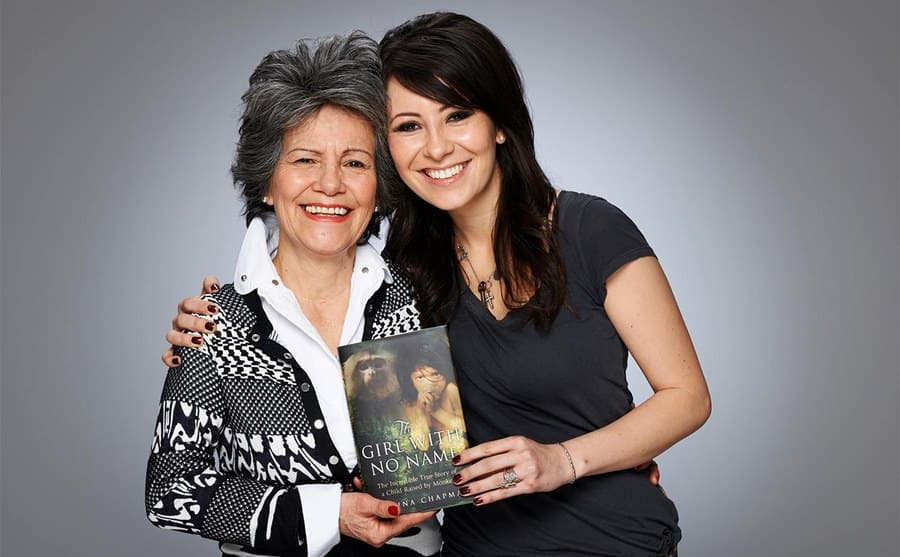 Marina and her daughter posing with her book titled 'The Girl With No Name.'