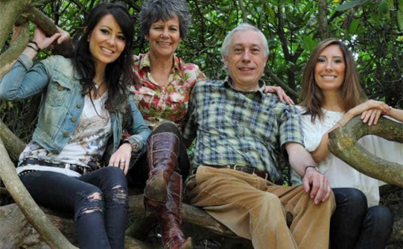 Marina with her husband and two daughters posing in tree roots