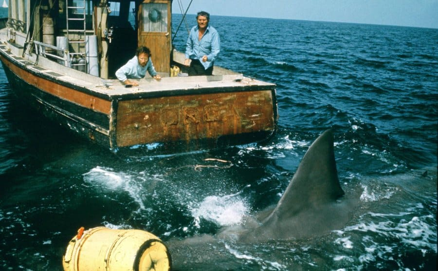 Richard Dreyfuss and Robert Shaw on a boat during the filming of Jaws with a shark swimming by the back of their boat