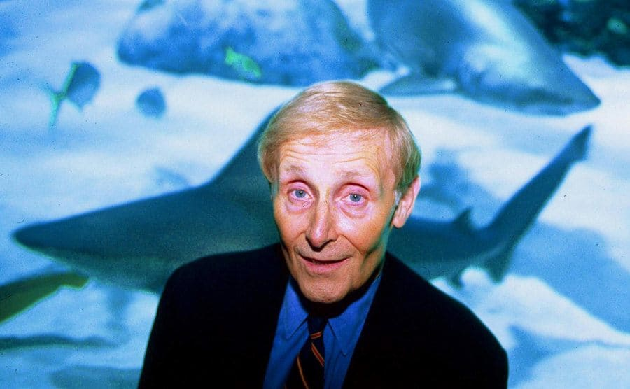 Peter Benchley in front of a shark tank