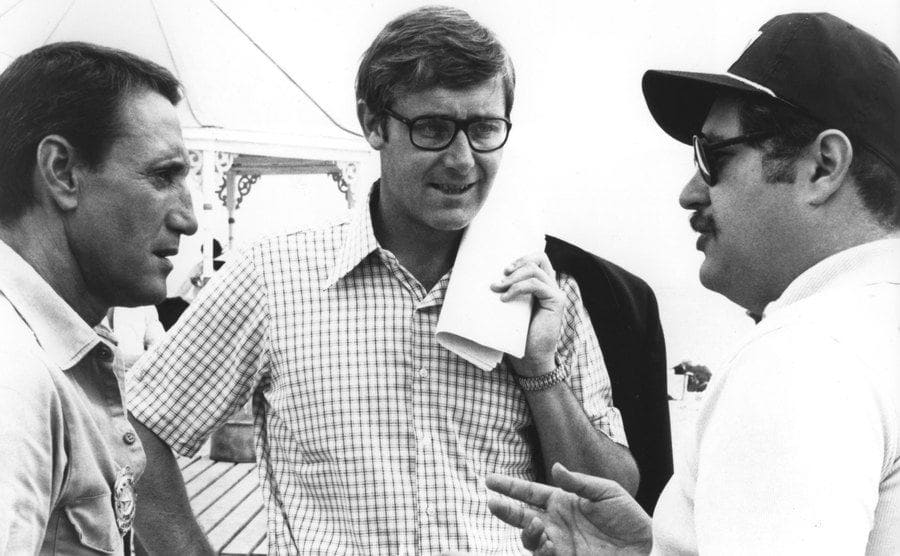 Roy Scheider, Peter Benchley, and Carl Gottlieb on the set of Jaws standing in a circle talking