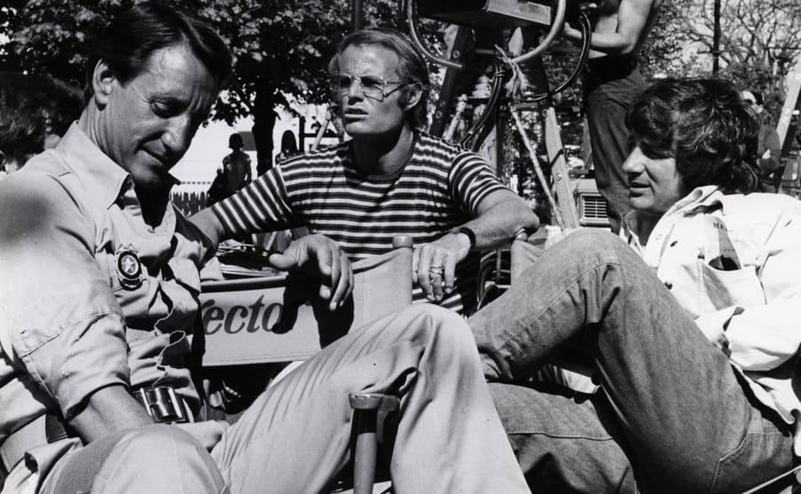 Roy Scheider, Richard Zanuck, and Steven Spielberg sitting around the cameras on the set of Jaws