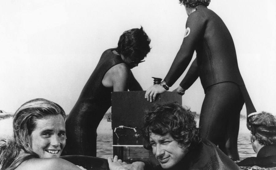 Susan Backlinie and Steven Spielberg with other crew members in the water behind the scenes of Jaws