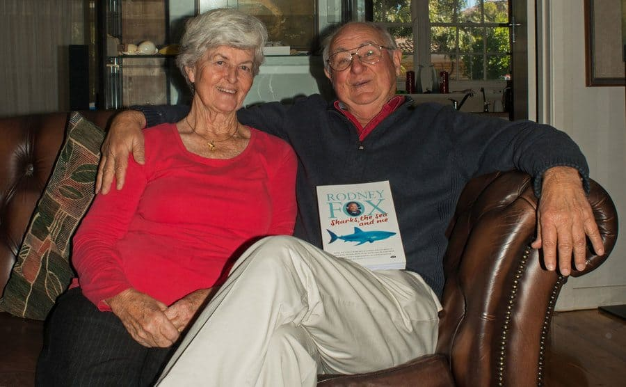 Rodney Fox and his wife sitting on the couch with his book 'Sharks, the sea and me' on his lap