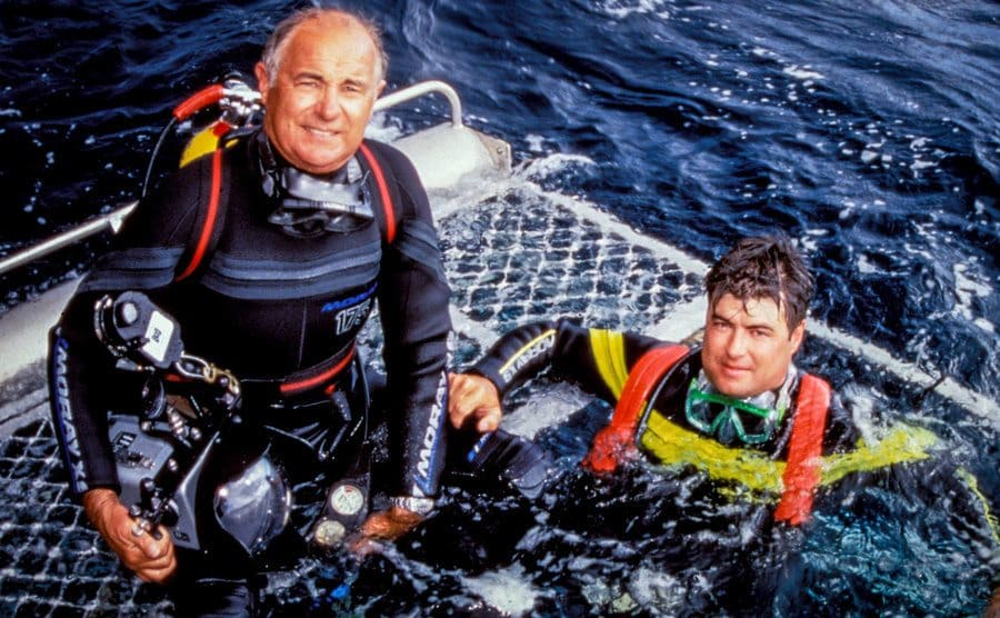 Andrew and Rodney Fox sitting on a cage wearing diving gear