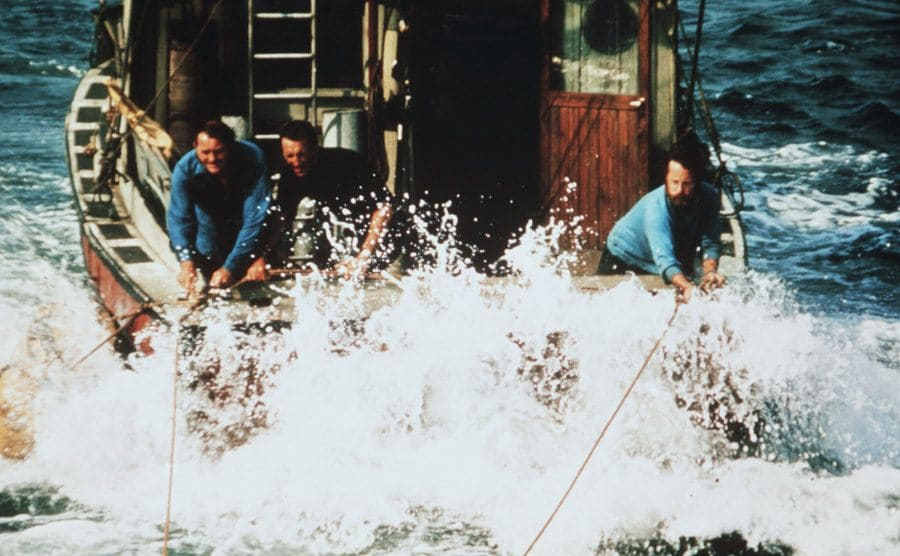 Robert Shaw, Roy Scheider, and Richard Dreyfuss holding onto ropes from the back of a speeding boat
