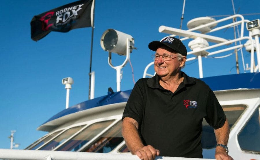 Rodney Fox standing on the side of a boat with his name on the flag, his t-shirt, and baseball cap